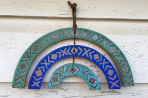 Rainbow hanging made with hand-cut cone 6 red clay tiles. Hand painted wax resist design with vibrant glazes $45