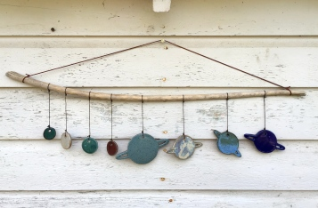 Solar system wall hanging made with hand-cut cone 10 stoneware tiles, various glazes. Hung on driftwood $80