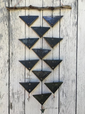 Triangle wall hanging with hand-cut triangle cone 10 stoneware tiles with silver-black glaze. Hung with driftwoodand copper wire, with copper beads and mirror accents $120