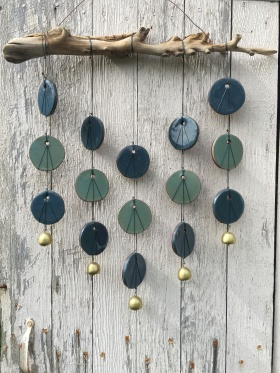 Wall hanging made with hand-cut cone 10 stoneware tiles, hung on driftwood, with metal bell accents $200